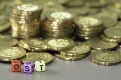 Monete del testo e di oro di GST Immagine Stock
