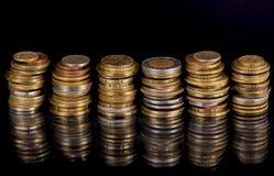 Monete della pila sopra fondo nero Fotografia Stock Libera da Diritti