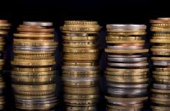 Monete della pila sopra fondo nero Immagini Stock Libere da Diritti