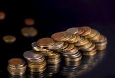 Monete della pila sopra fondo nero Fotografia Stock
