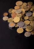 Monete della pila sopra fondo nero Immagine Stock Libera da Diritti