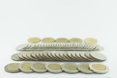 Monete della Tailandia di baht impilate su fondo bianco Immagine Stock
