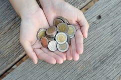 Monete della tenuta delle donne sulla tavola di legno immagini stock