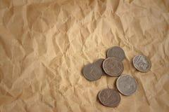 Monete di baht della Tailandia su fondo di marrone chiaro Fotografia Stock