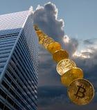 Monete di Bitcoin che cadono dalla costruzione Immagine Stock