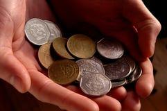 Monete di Colones dalla Costa Rica in due mani Fotografie Stock Libere da Diritti