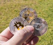 Monete di Cryptocurrency in una mano; Bitcoin, ondulazione, un poco Fotografie Stock Libere da Diritti