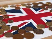 Monete di libbra, Regno Unito sopra la bandiera Fotografie Stock Libere da Diritti