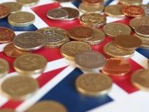 Monete di libbra, Regno Unito sopra la bandiera Immagine Stock