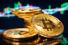 Monete di oro di Bitcoin su un fondo del grafico del mercato fotografia stock