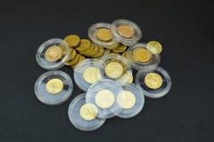 Monete di oro in capsule di plastica Fotografie Stock