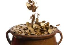 Monete di oro che cadono nel vaso d'annata Fotografie Stock