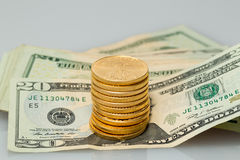 Una pila di $20 banconote in dollari con le monete di oro Fotografia Stock Libera da Diritti