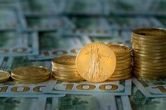 Monete di oro impilate sulle nuove banconote in dollari di progettazione 100 Fotografie Stock