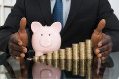 Monete di With Piggybank And dell'uomo d'affari Fotografia Stock Libera da Diritti