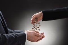 Monete di versamento dell'uomo d'affari sulla mano del collega Immagini Stock