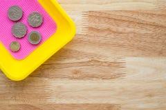 Monete di Yen giapponesi in vassoio variopinto della moneta sulla tavola di legno Fotografie Stock