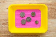 Monete di Yen giapponesi in vassoio variopinto della moneta sulla tavola di legno Fotografia Stock Libera da Diritti
