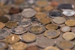 Monete differenti sul ripiano del tavolo di legno, mucchio del concetto delle monete Immagini Stock Libere da Diritti