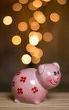 Monete dorate che entrano nel porcellino salvadanaio Fotografia Stock Libera da Diritti