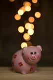 Monete dorate che entrano nel porcellino salvadanaio Fotografie Stock Libere da Diritti