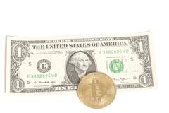 Monete dorate del bitcoin su un U S Dollaro Fotografie Stock Libere da Diritti