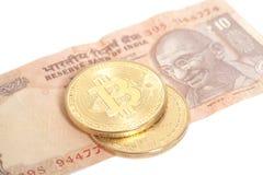 Monete dorate di Bitcoin sull'indiano dieci rupie Fotografia Stock