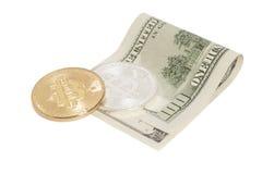 Monete dorate e d'argento del bitcoin e cento banconote del dollaro Immagine Stock