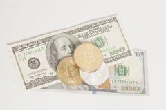 Monete dorate e d'argento del bitcoin e cento banconote del dollaro Fotografia Stock