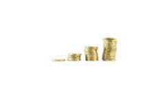 Monete dorate impilate su fondo bianco isolato Fotografia Stock Libera da Diritti