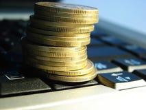 Monete dorate sul computer portatile Fotografia Stock Libera da Diritti
