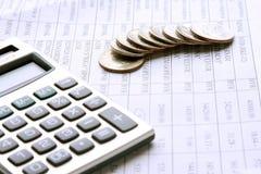 Monete e calcolatore sulle carte d'ufficio Fotografia Stock