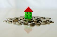 Monete e casa che stanno su  Immagini Stock