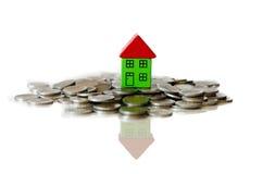 Monete e casa che stanno su  immagini stock libere da diritti