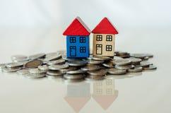 Monete e case che stanno su  Immagine Stock Libera da Diritti