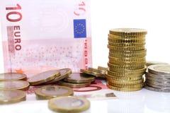 Monete e fatture europee su fondo bianco Fotografia Stock