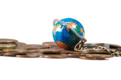 Monete e globo sulla catena su priorità bassa bianca Fotografia Stock