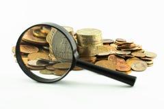 Monete e lente d'ingrandimento Immagini Stock