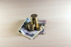Monete e 100 rupie di note sulla tavola di legno immagine stock libera da diritti