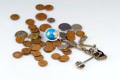 Monete e tasto con il globo sulla catena fotografia stock