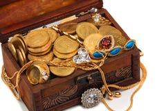Monete e tesori di oro in un petto di legno immagini stock