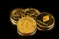 Monete fisiche di colore dell'oro delle valute cripto comuni nella luce intensa sulla superficie nera dello specchio immagine stock