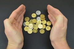 Monete fra le mani dell'uomo su fondo nero Monete bronzee Fotografia Stock