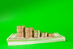 Monete impilate in barre su una pila di 100 fatture del dollaro Fotografia Stock Libera da Diritti