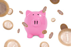 Monete intorno al porcellino salvadanaio Fotografie Stock
