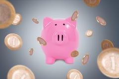 Monete intorno al porcellino salvadanaio Fotografia Stock Libera da Diritti