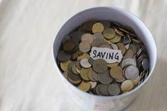 Monete in latta con note scritte dal ` di risparmio del ` di parola immagine stock