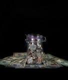 Monete in Mason Jar su una valuta del letto Fotografie Stock