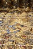 Monete messe sull'orma di Buddha Fotografie Stock