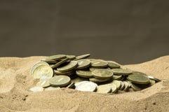 Monete nella sabbia immagini stock libere da diritti